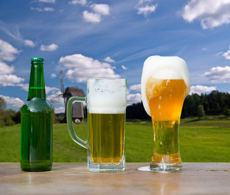Pouring glass of beer from bottle on landscape background