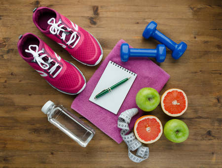 Fitness concept with sneakers dumbbells pomelo bottle of water apple and measure tape on wooden table background