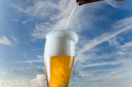 Pouring glass of beer from bottle on blue sky background Stock Photo