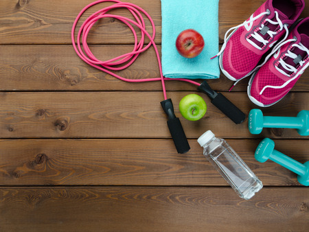 Fitness concept with sneakers bottle of water apple and skipping rope on wooden table background Stock Photo