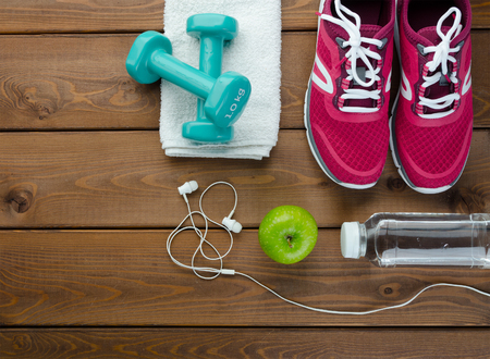 Fitness concept with sneakers dumbbells bottle of water and apple on wooden table background