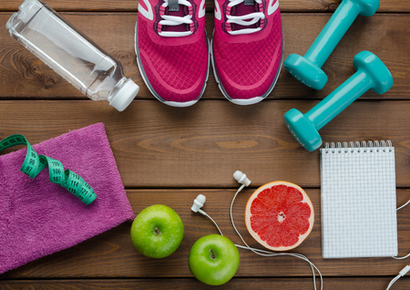 Fitness concept with sneakers dumbbells bottle of water apple pomelo and measure tape on wooden table background      0705 Stock Photo