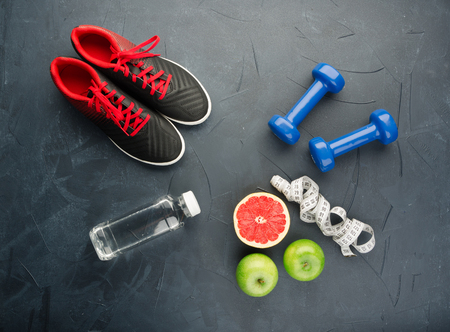 Fitness concept with sneakers dumbbells pomelo bottle of water apple and measure tape on black concrete background Stock Photo