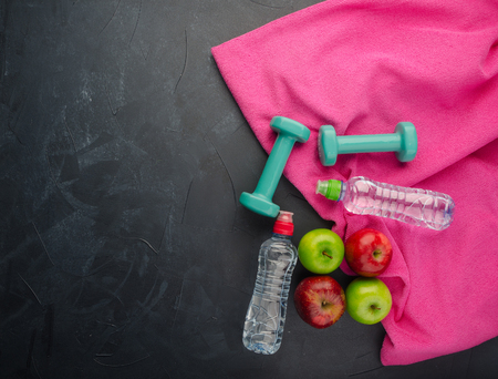 Healthy lifestyle concept. colored Apples dumbbells sport water bottles and purple towel on black concrete background