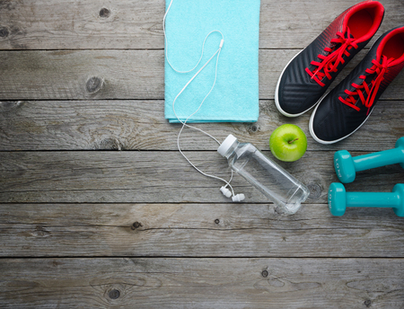 Fitness concept with sneakers dumbbells bottle of water apple and audio headphones, on old wooden table background