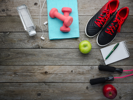 Fitness concept with sneakers dumbbells bottle of water apple and measure tape on old wooden table background