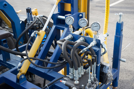 Hydraulic tubes fittings and manometers on control panel of lifting mechanism Stock Photo