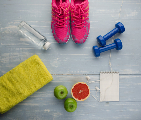Fitness concept with sneakers dumbbells bottle of water apple pomelo and measure tape on blue wooden table background