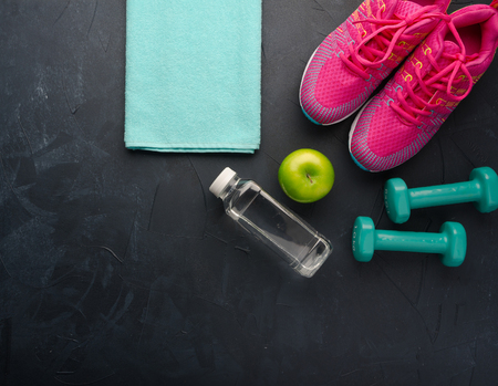 Fitness concept with sneakers dumbbells bottle of water and apple on black concrete background