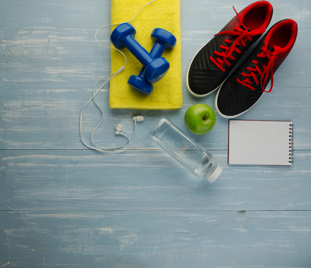 Fitness concept with sneakers dumbbells bottle of water apple and audio headphones, on blue wooden table background