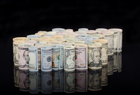 Dollar banknotes rolls on black background with reflection. Business and financial concept with usa dollar banknotes.