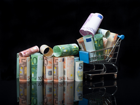 Euro rolls and shopping cart full packs of bills on black background with reflection. Business and financial concept with euro banknotes. Stock Photo