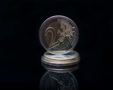 Euro currency coin macro photo with reflection on black background. Business and financial concept with Euro coins.