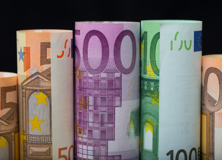European paper money in rolls on black background. Business and financial concept with euro banknotes.