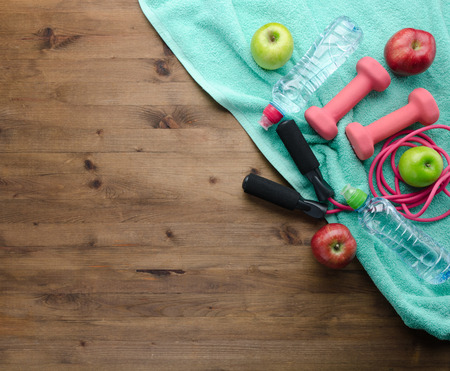 Fitness concept with Apples dumbbells towel bottle of water  skipping rope  and measure tape on wooden table background