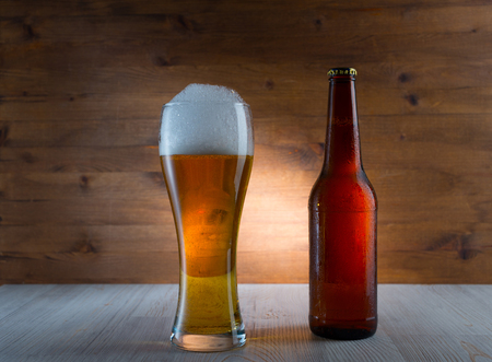 Glass of golden beer and bottle on wood background