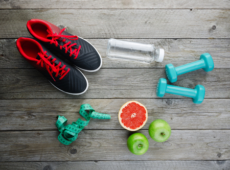 Fitness concept with sneakers dumbbells pomelo bottle of water apple and measure tape on old wooden table background Stock Photo