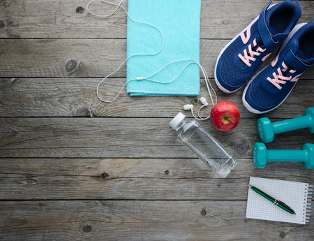 Fitness concept with sneakers dumbbells bottle of water apple and measure tape on old wooden table