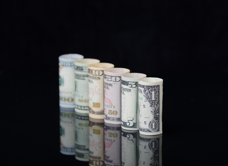 US dollars banknotes rolls on black background with reflection. Creative business and financial concept with usa dollar banknotes.