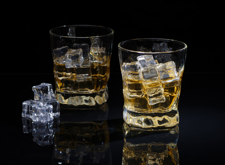 Two stylish glasses of whiskey with ice cubes on black background with reflection
