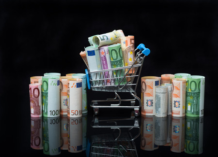 Euro money rolls and shopping cart full packs of bills on black background with reflection. Business and financial concept with euro banknotes.