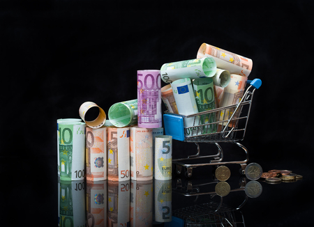 Euro money rolls and shopping cart full packs of bills on black background with reflection. Business and financial concept with euro banknotes and coins.