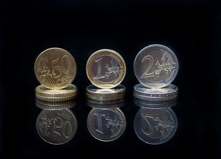 European currency coin macro with reflection on black background. Business and financial concept with Euro coins. Stock Photo