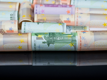 European paper money in rolls on black background with reflection. Business and financial concept with euro banknotes. Selective focus. Stock Photo