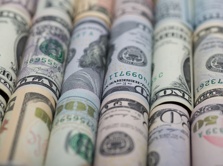 Background of the different  American dollar bills in rolls. Business and financial concept with us dollars banknotes. Selective focus.