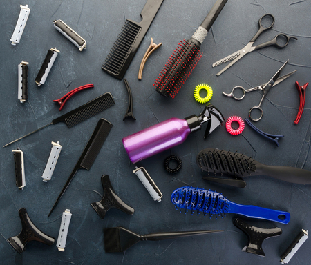 Top view of professional hair dresser tools on black concrete background
