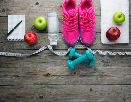 Fitness concept with sneakers dumbbells bottle of water and apple on old wooden table