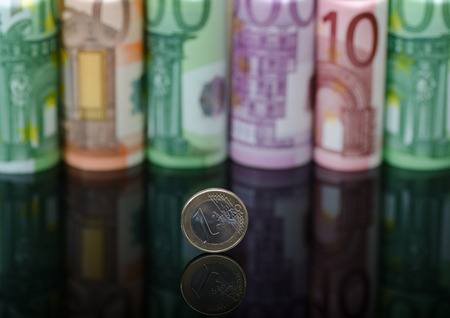 European paper money in rolls and coins on black background with reflection. Business and financial concept with euro banknotes.