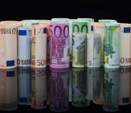European paper money in rolls  on black background with reflection. Business and financial concept with euro banknotes. Stock Photo