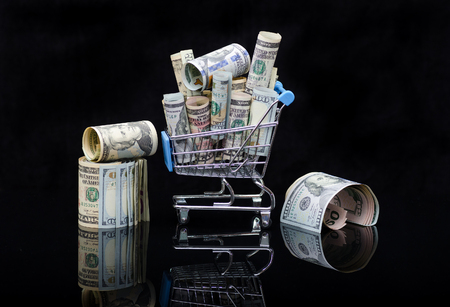 US dollars rolls and shopping cart full packs of bills on black background with reflection. Creative business and financial concept with usa dollar banknotes .