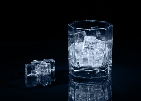 Ice cubes in empty glass on dark background. Stock Photo