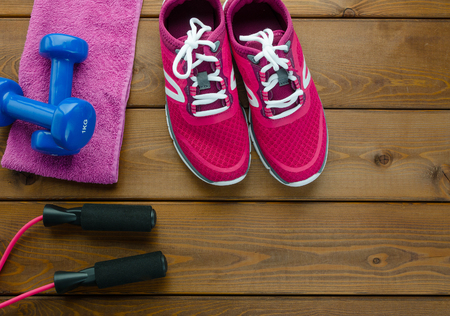 Fitness concept with sneakers dumbbells towel and Skipping rope on wooden table background 写真素材