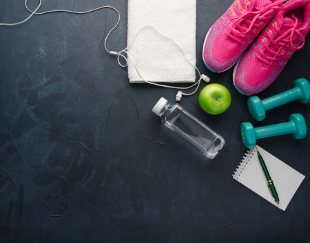 Fitness concept with sneakers dumbbells bottle of water apple and headphones on black concrete background 写真素材