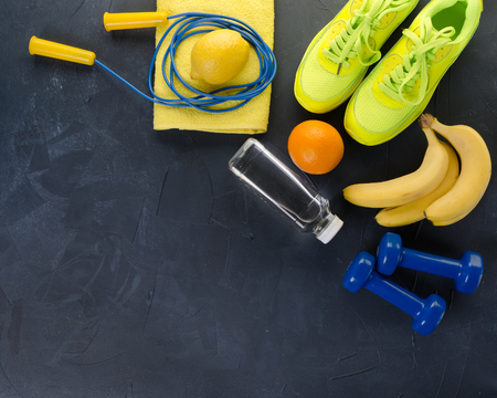 Fitness concept with sneakers dumbbells towel bottle of water bananas oranges and lemons on black concrete background 写真素材