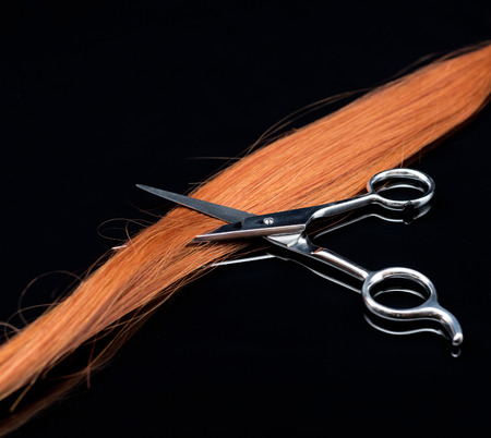Red curl of natural hair and scissors on black background  with reflection.