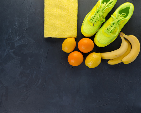 Fitness concept with sneakers towel bananas oranges and lemons on black concrete background
