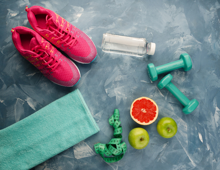 Fitness concept with sneakers dumbbells bottle of water apple and measure tape on multicolored background