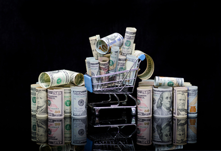 US dollars rolls and shopping cart full packs of bills on black background with reflection. Creative business and financial concept with usa dollar banknotes
