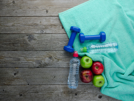 Healthy lifestyle concept. colored Apples dumbbells sport water bottles and turquoise towel on old wooden table