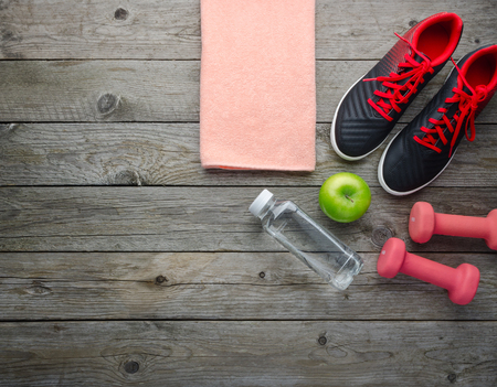 Fitness concept with sneakers dumbbells bottle of water and apple on old wooden table background
