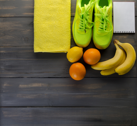 Fitness concept with sneakers towel bananas oranges and lemons on black wooden background Фото со стока