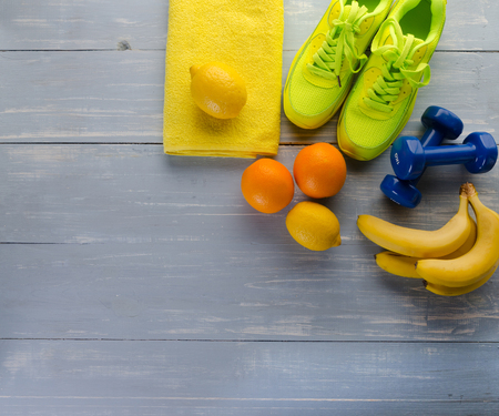 Fitness concept with sneakers dumbbells towel bananas oranges and lemons on blue wooden table background.