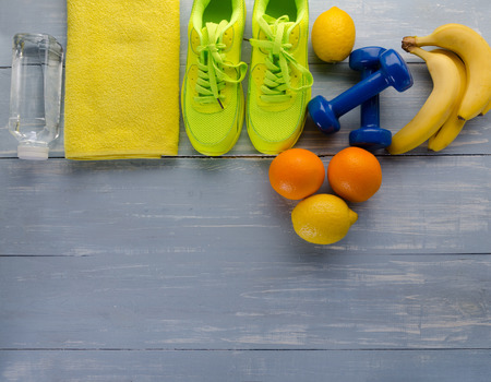 Fitness concept with sneakers dumbbells towel bottle of water bananas oranges and lemons on blue wooden table background.