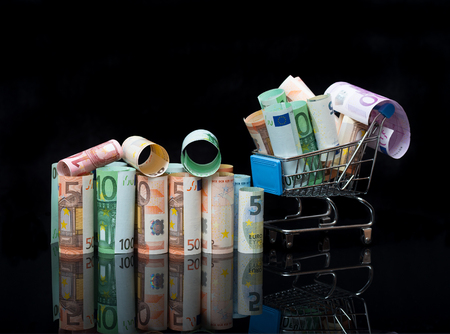 Euro money rolls and shopping cart full packs of bills on black background with reflection. Business and financial concept with euro banknotes