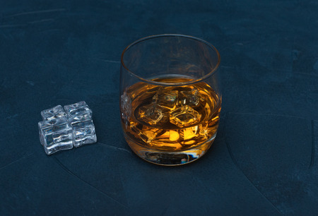 Glass of whiskey with ice cubes on dark blue concrete background Фото со стока