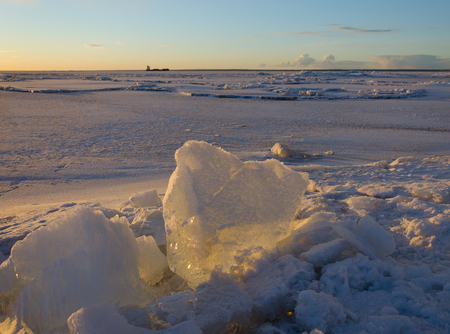 Melting pieces of thick ice on frozen sea at sunset time